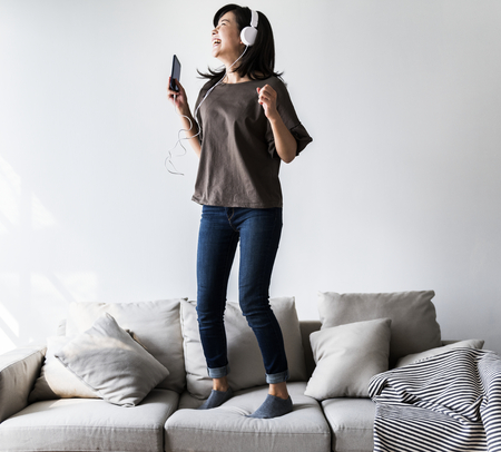 Asian woman enjoying music at home Stock Photo