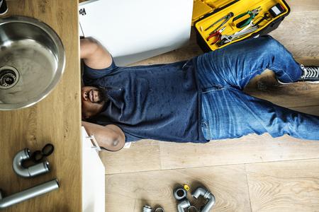 キッチンシンクを固定する男