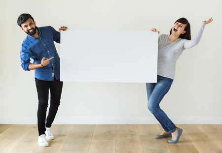 Man and woman holding blank board copyspace