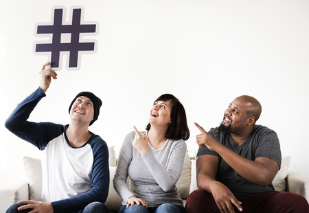 Group of diverse friends sitting on couch holding a hashtag icon
