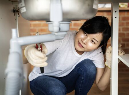 Asian woman fixing kitchen sink