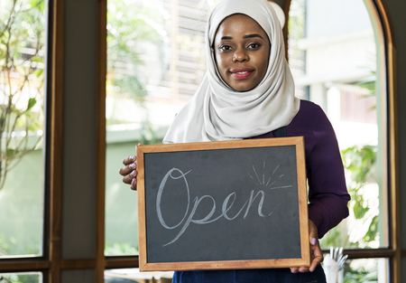 Muslim woman holding a chalkboard with the word Open 版權商用圖片