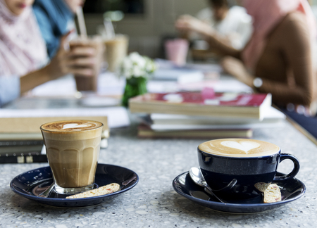 Two cups of coffee with group gathering in the background Stock Photo