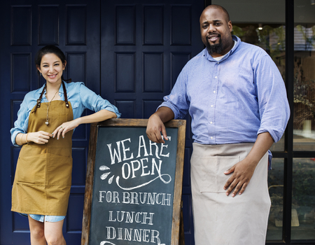 Cheerful business owners standing with open blackboard