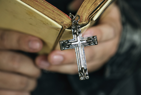 Close up of a man reading a bible with cross hanging religion and belief concept