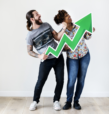 Happy smiling interracial couple holding a growth arrow growth and success concept