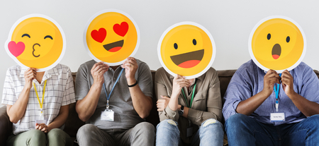 Group of co-workers holding emoticons