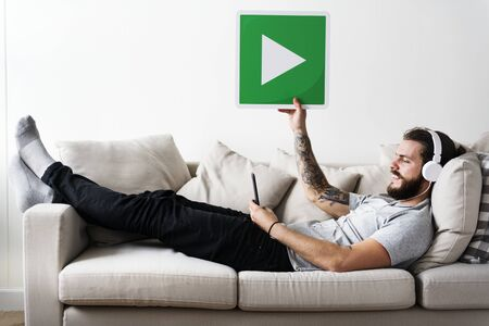 Caucasian man enjoying music at home holding a play button