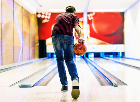 Boy about to roll a bowling ball hobby and leisure concept Imagens