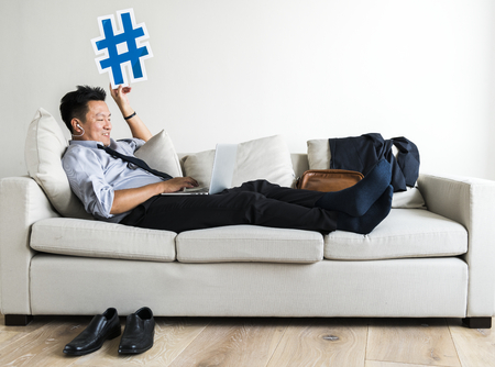 Asian businessman taking break laying on couch Stock Photo