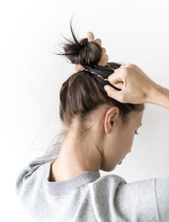 Woman making hair bun 版權商用圖片 - 99216926