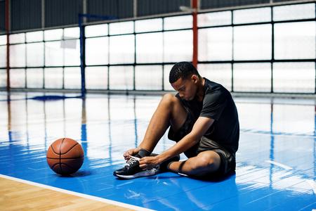 African American Teenager binden seine Schnürsenkel auf einem Basketballplatz Standard-Bild - 99217101