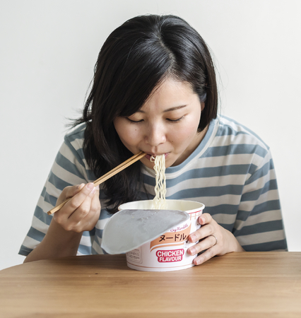 Asian woman eating an instant noodle