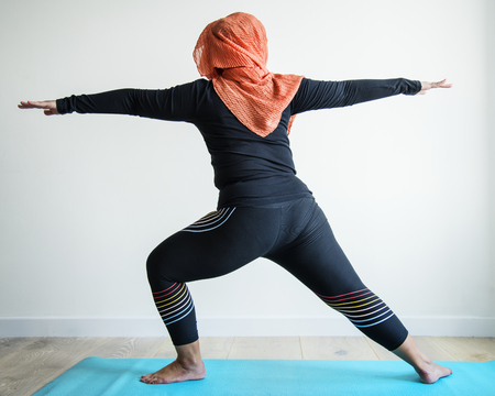 Rear view of muslim woman doing yoga