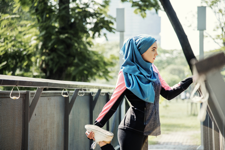 Muslim woman doing exercise outdoors Stock Photo