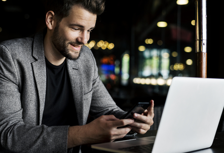 Man reading messages on his phone Stock Photo
