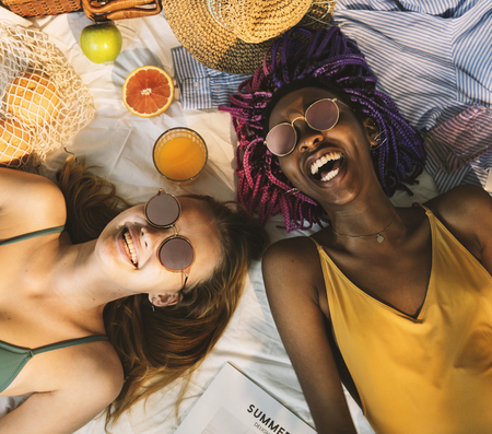 Cheerful girls in swimsuit sun tanning together Stock Photo