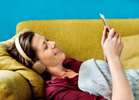 Woman listening to music on the sofa Stock Photo