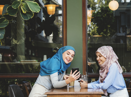 Muslim women hanging out in a coffee shop 版權商用圖片 - 115871285