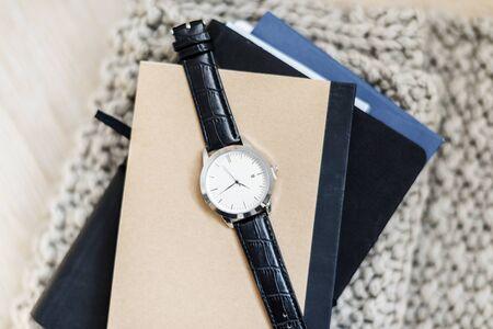 Closeup of watch on notepads