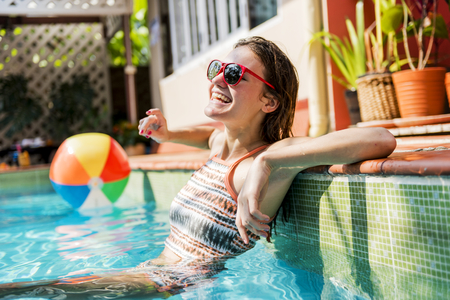 Girl cooling down in a swimming pool Stock Photo