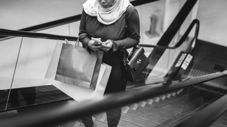 Muslim woman using a mobile phone on escalator Stock fotó