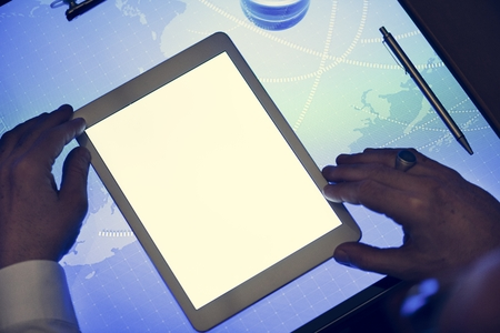 Hands holding using tablet on a cyber space table 写真素材