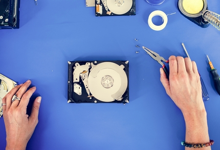 Hands holding tool fixing HDD at electronics repair shop Stock Photo