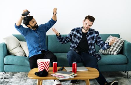 Men playing video game on sofa