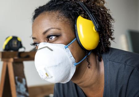 Zwarte vrouw die oorbescherming draagt Stockfoto - 100099972