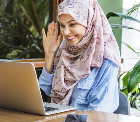 Muslim woman using video chat in a coffee house
