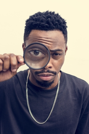 African man playing with a magnifying glass