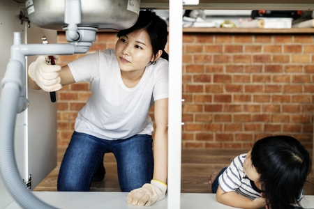 Asian family fixing kitchen sink Foto de archivo