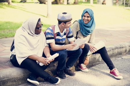 Muslim students sitting by the roadside