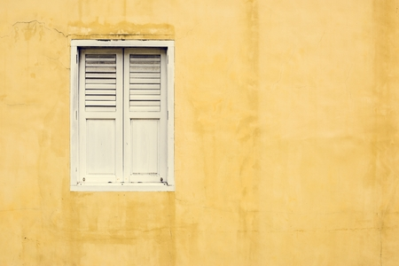 Yellow wall and a white window Imagens