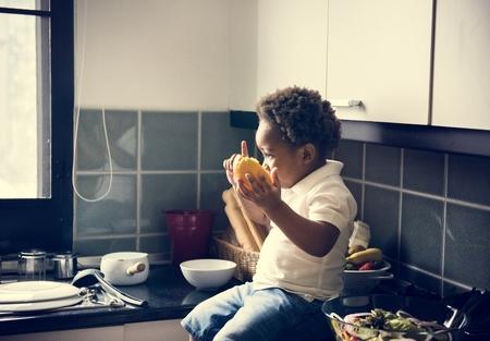 Black kid with orange in the kitchen