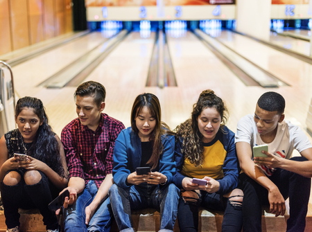 Group of teenage friends using smartphone in a bowling alley