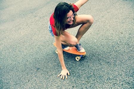 Closeup of a Caucasian woman skateboarding Imagens