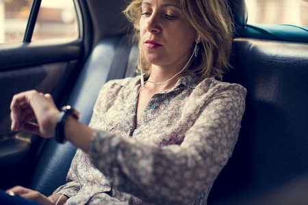 Blond woman sitting in a taxi Imagens