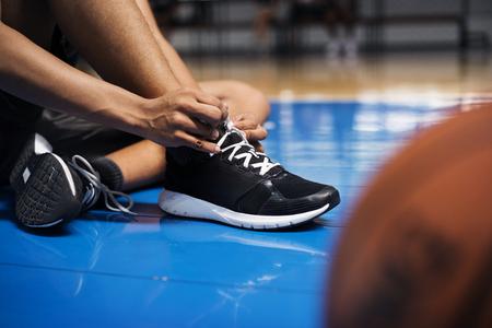 Ragazzo adolescente afroamericano che lega i suoi lacci delle scarpe su un campo da basket