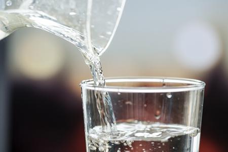 Colpo a macroistruzione di versamento dell'acqua in un vetro