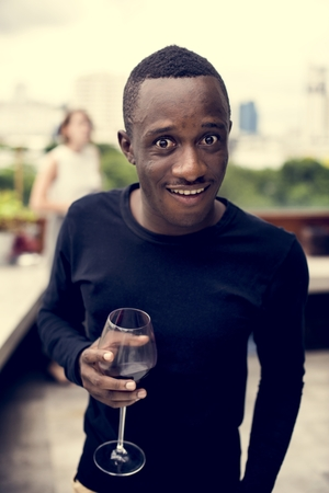 African man holding a wine glass