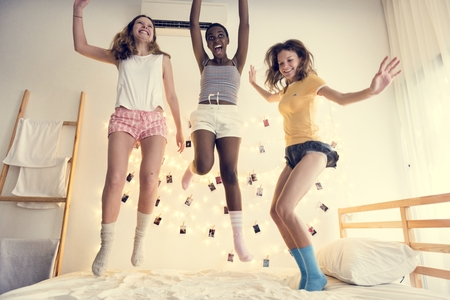 A group of diverse women jumping on bed together