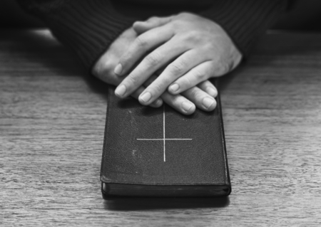 Hands over bible on wooden table Stock Photo