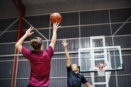 Two teenage boys playing basketball together on the court Stock Photo
