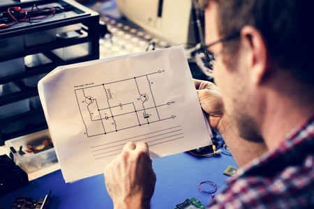 Technician man looking at resistor circuit on paper