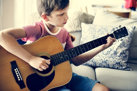 Young boy playing guitar 写真素材