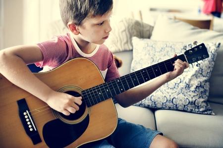 Young boy playing guitar Stok Fotoğraf
