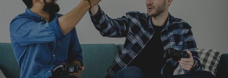 Men playing video game on sofa giving each other a high five leisure and teamwork concept
