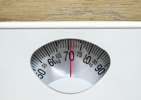 Closeup of weight scales overweight and obesity concept Фото со стока